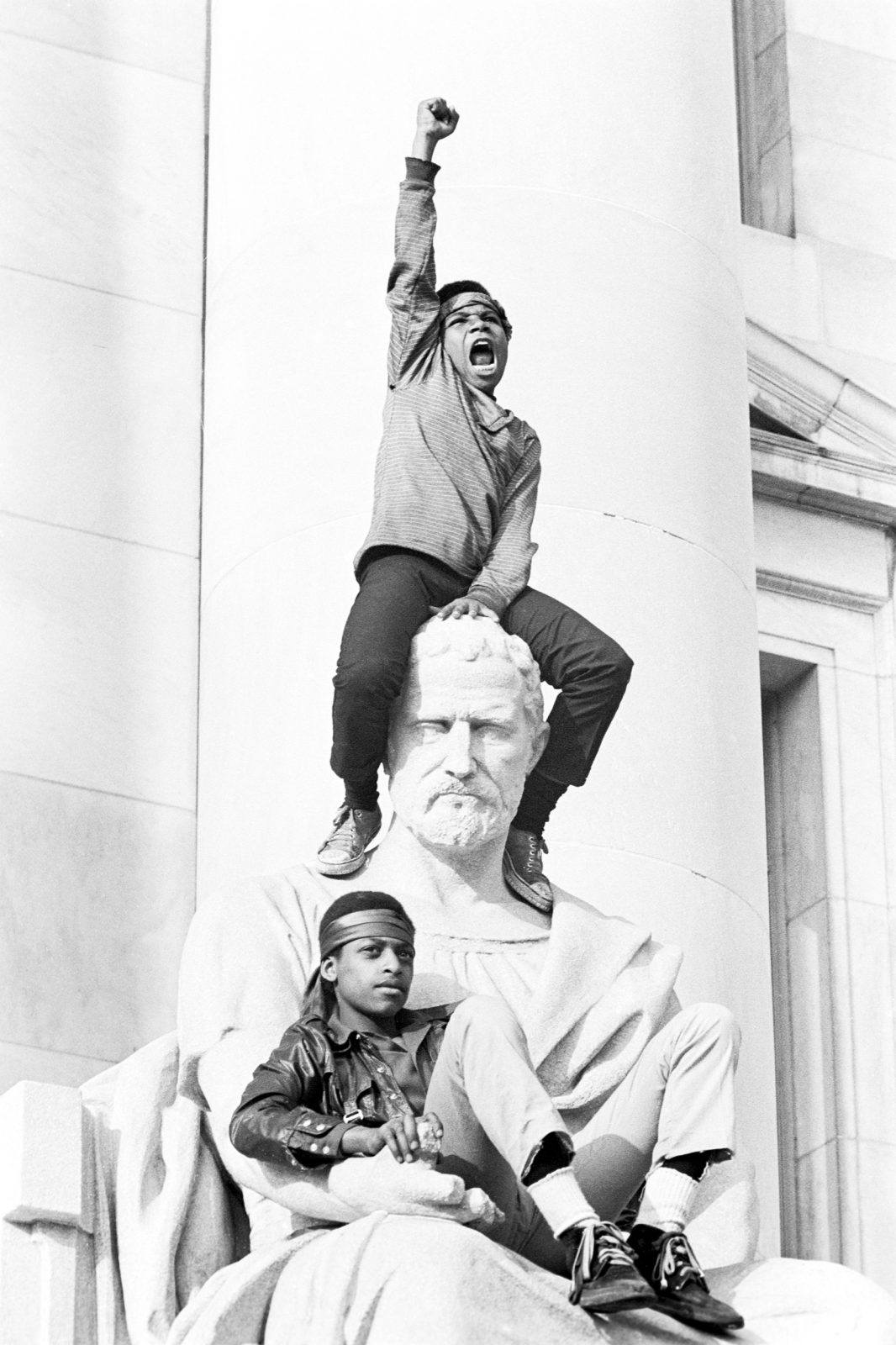 Boy gives raised fist salute as he and a friend sit on a statue in front of the courthouse during the Bobby Seale trial.